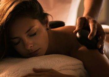 The girl enjoys stone therapy treatment. Massage with hot basalt stones. Spa treatment. Beautiful charming light.